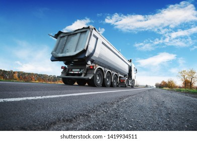 Big white dump truck on the countryside road against blue sky with clouds