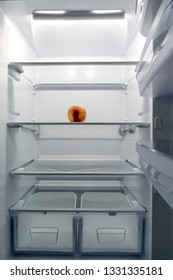 A big white fridge is almost empty, only a peach is in it. It is urgent to buy groceries.