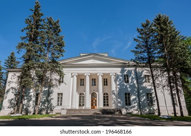 Big white house with columns in the park on a background of blue sky