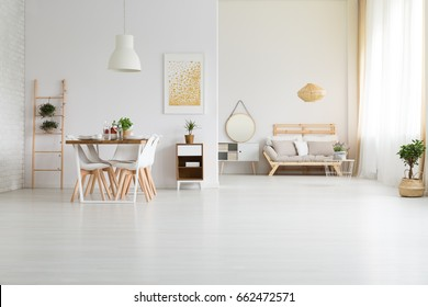 Big, white loft space with stylish wooden furniture