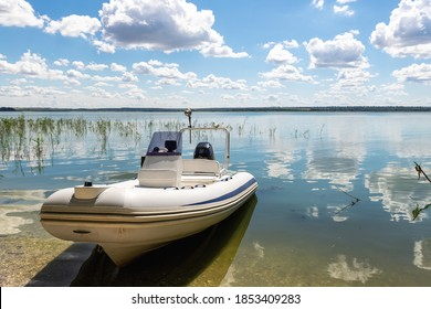 Big white modern fishing motorboat moored at lake or river shore sand pebble beach against scenic blue sky on bright sunny summer day. Inflatable boat parked on pond bank after water surface trip