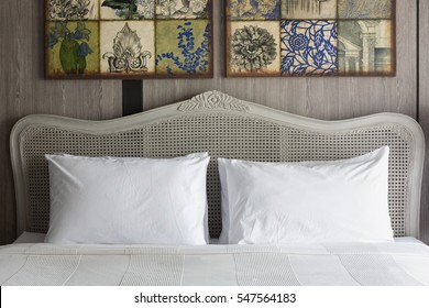 Big white pillows on a white luxury bed with rattan headboard.