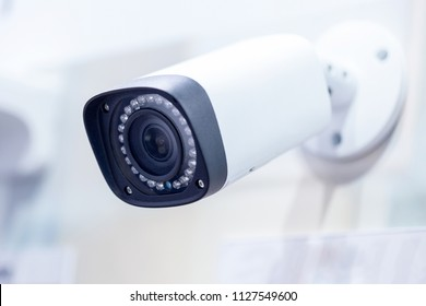 Big white professional surveillance camera. CCTV mounted on ceiling. LED IR lights around lens. Security system concept. Copyspace, neutral light blue backgound