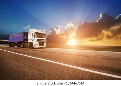 Big white truck with blue trailer on the countryside road against night sky with sunset