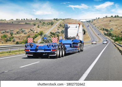 A big white truck with a heavy equipment flatbed trailer with other cars on a countryside road against a blue sky with clouds