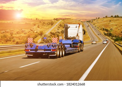 A big white truck with a heavy equipment flatbed trailer with other cars on a countryside road in motion against a night sky with a sunet