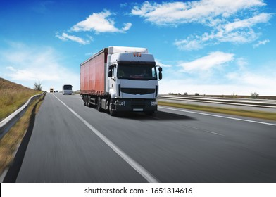 A big white truck with a red trailer and other cars on the countryside road in motion against a blue sky with clouds