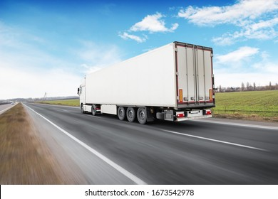 A big white truck and a trailer with space for text on the countryside road in motion against a blue sky with clouds