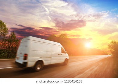 Big white van in motion on the countryside road shipping goods against night sky with sunset