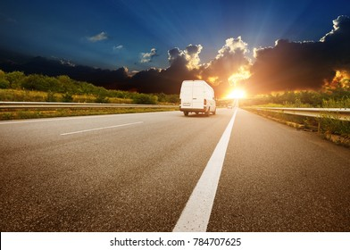 Big white van on the countryside road shipping goods against night sky with sunset