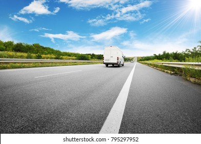 Big white van on the countryside road shipping goods against blue sky with sun