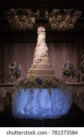 Big white wedding cake in ballroom hall decoration with flower cream in vintage color tone