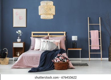 Big wicker lampshade hanging above wooden bed with pastel colored bedding