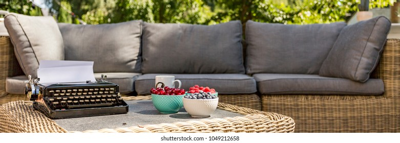 Big wicker sofa with grey pillows with wicker coffee table in front. On the coffee table old typing machine and bowls of fruits