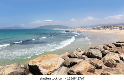 The big and wide beach of Tarifa in summer. It is a beautiful day with sunshine, blue skies and gentle waves from the Atlantic. There are large stones in the foreground.