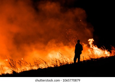 Big wildfire at night with man on foreground.