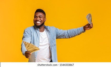 Big Win. Overjoyed African American Man Holding A Lot Of Money In Both Hands On Yellow Background, Panorama