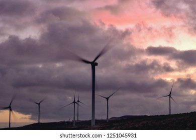 Big wind wheels against purple pink sky just after sunset on Tenerife. Partial view of a wind farm, the blades of wind turbines turn fast, the sky is covered with purple gray clouds, backlit shot.