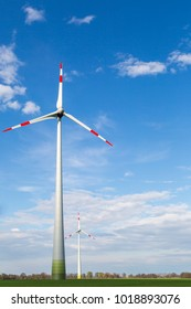 big windmills stand on a field and produce green electricity