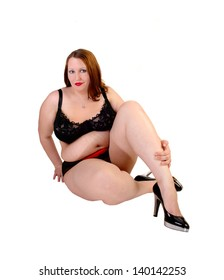 A big woman in black lingerie and high heels sitting on the floor in the  studio for white background.