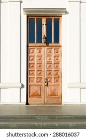 Big wooden church closed door and white walls