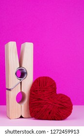 Big wooden clothespin and red heart. Toy heart and clothespin on pink background. St. Valentine's Day