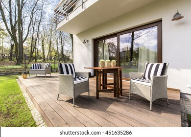 Big wooden cozy porch with chairs and coffee table in the back of big residence
