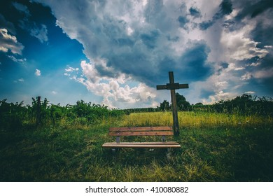 big wooden crucifix in the field with dramatic clouds