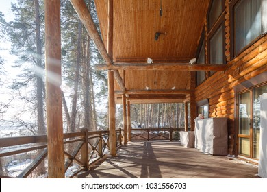 big wooden terrace in traditional chalet with panoramic windows and pine forest around