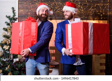 Big wrapped box with ribbon. Great surprise. Prepare huge surprise gift. Men compete who has larger size. Bigger gift battle. Men santa carry big gift boxes. Size matters. Biggest gift for christmas.