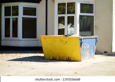 Big yellow & blue skip rubbish bin in front of office building. Focus on the bright bin with shadow on the concrete floor. Renovation, moving concept. Space to add text on surrounding background.