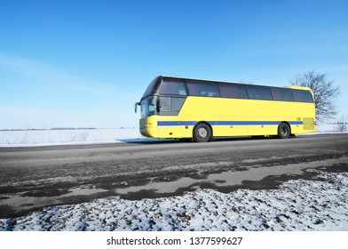 Big yellow bus on a winter countryside road with snow against a blue sky