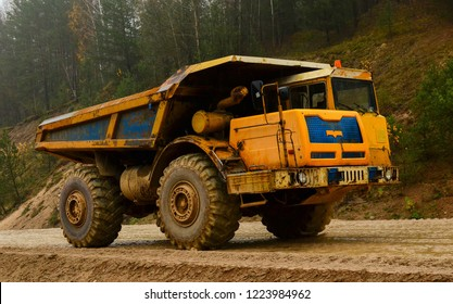 Big yellow diesel quarry dumper at work. Heavy mining truck transporting sand and clay. Belaz.