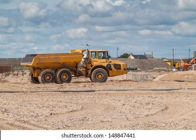 A Big Yellow Dump Truck on a Beach Construction Site