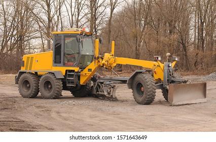big yellow grader on road construction