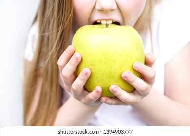Big yellow green apple in children's hands . Girl biting the apple