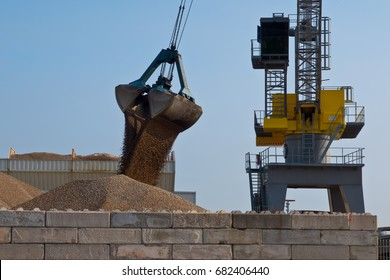 Big yellow harbor crane is unloading sand from a ship