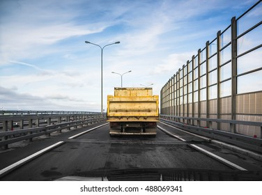 Big yellow industrial tipper truck goes on asphalt road, rear view from other car cabin