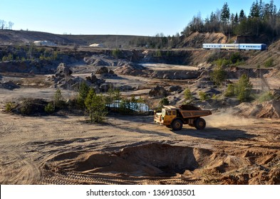 Big yellow mining truck transporting sand in an open-pit mining quarry, top view - image