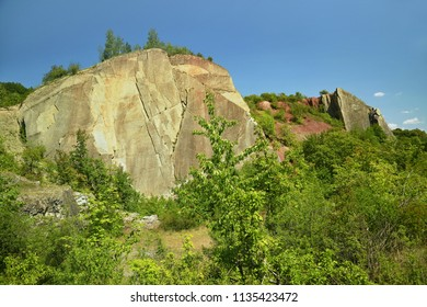Big yellow and red perpendicular rocks standing in Hlubocepy, Prague, Europe, former limestone quarry, green trees and bushes, sunny summer day, blue sky