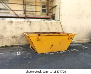 Big yellow rubbish skip on side of road. Selective focus on heavy metal industrial bin with blurry scaffolding, dirty wall in background. Space to add text on road surface. Renovate building concept.