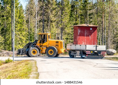 Big yellow tractor relocates old small red woden house in the trailer, sunny summer day, nearby to Umea city, North Sweden