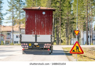 Big yellow tractor relocates old small red woden house in the trailer, sunny summer day, nearby to Umea city, North Sweden.Road construction sign at the road side