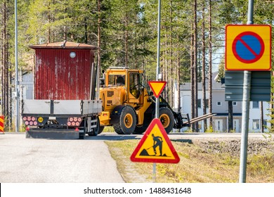 Big yellow tractor turn right while relocates old small red woden house in the trailer, sunny summer day, nearby to Umea city, North Sweden.Road construction sign at the road side