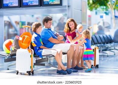 Big young family with three kids traveling by airplane at Dusseldorf International airport, parents with teenager boy, toddler girl and little baby holding colorful luggage for summer beach vacation