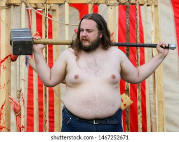 Big Zavidovo, Russia - July 19, 2019: A man with a sledgehammer at the rock festival Invasion.