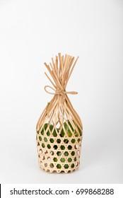 Bigarade oranges in round bamboo basket on white background