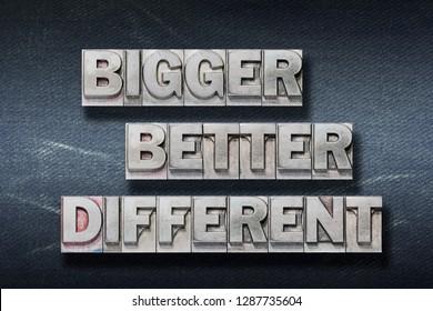 bigger, better, different words made from metallic letterpress on dark jeans background