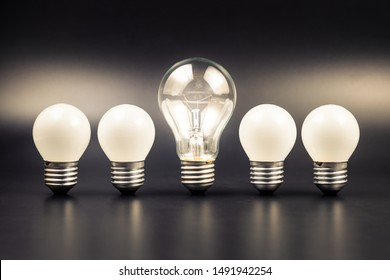 Bigger light bulb glowing in the middle of the row of small light bulbs, leader light bulb