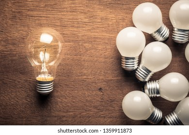 Bigger light bulb glowing out of the group of small light bulbs